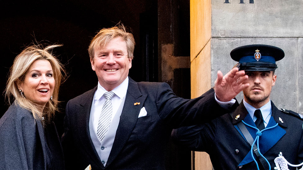 King Willem-Alexander of The Netherlands and Queen Maxima are pictured outside a building waving to the media, while a nearby guard salutes