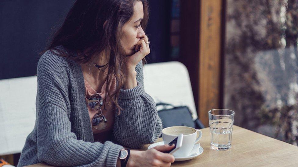 Una mujer depresiva y pensativa con un teléfono en la mano.
