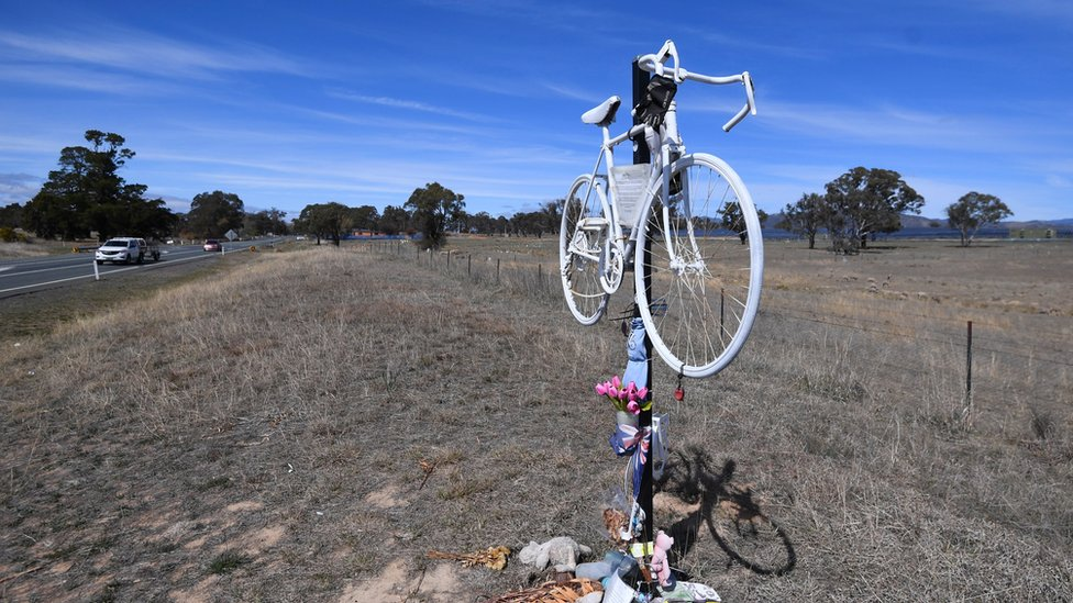 A bicycle and flowers placed in tribute to Hall at the site of the crash beside a highway