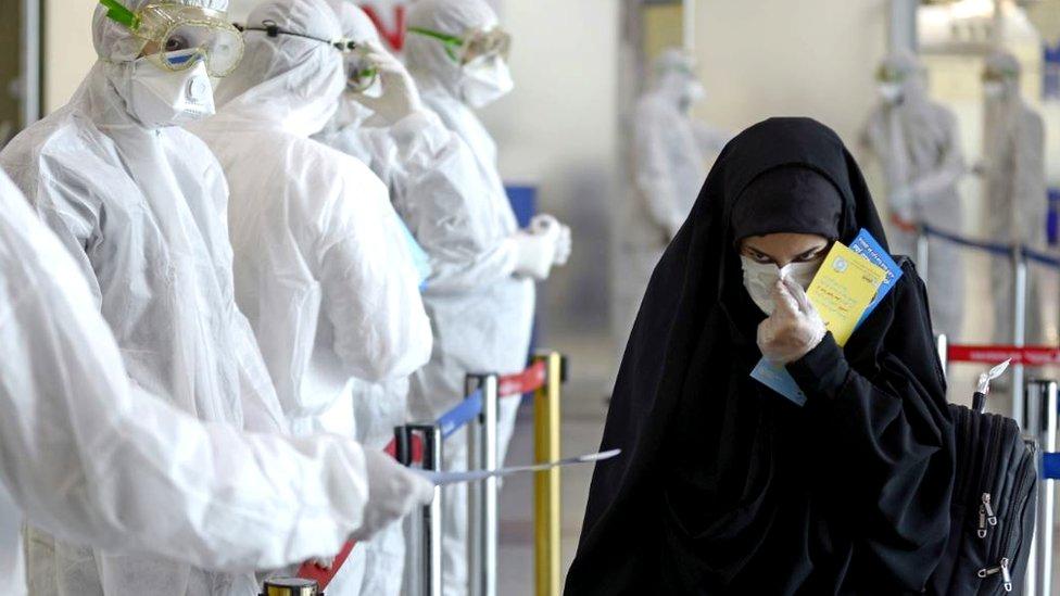 فريق طبي يرتدي معدات واقية ويوزع منشورات على المسافرين العراقيين العائدين من إيران، 5 مارس/آذار 2020