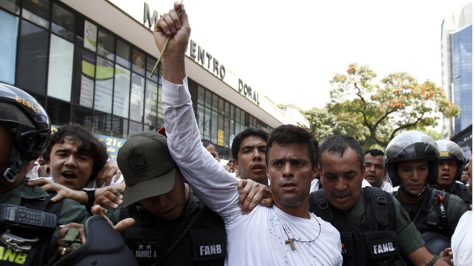 Leopoldo Lopez, dressed in white and holding a flower, is taken into custody by Bolivarian National Guards in Caracas, Venezuela, 18 February 2014