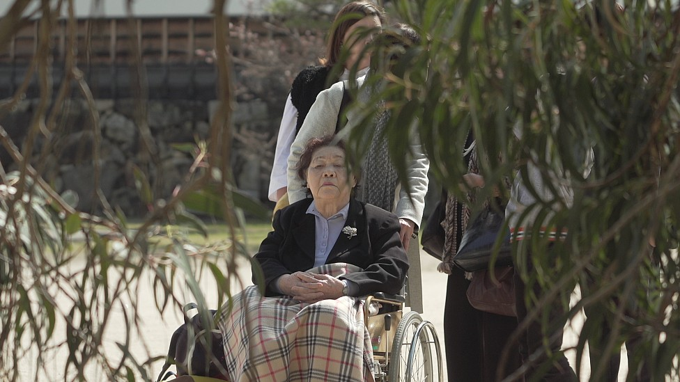 Teruko en silla de ruedas empujada por Tomoko en el jardín de Shukkeien