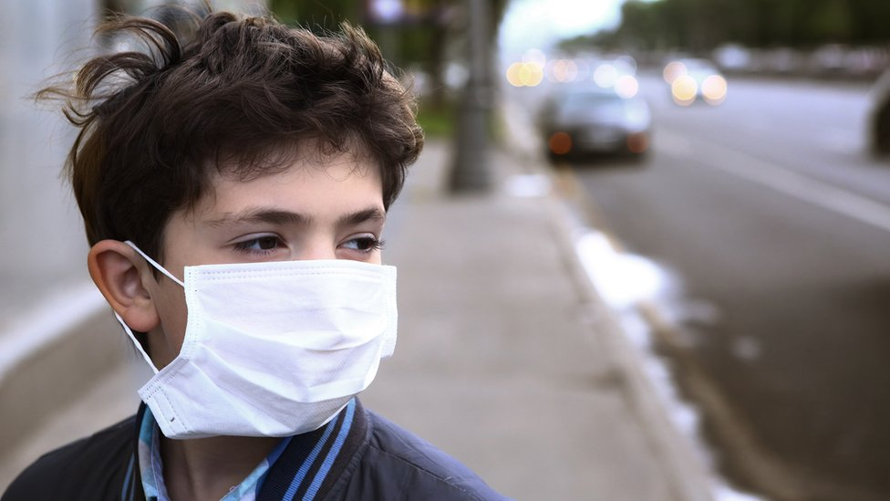 Boy wearing a face mask on a city street