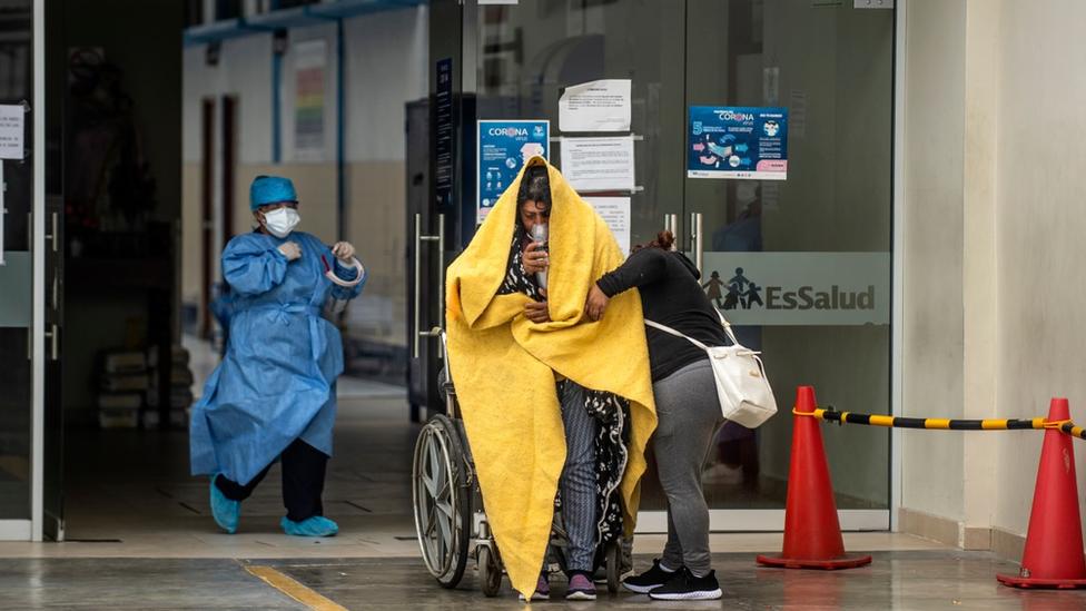 Un paciente de covid recibe asistencia médica a la entrada de un hospital en Perú