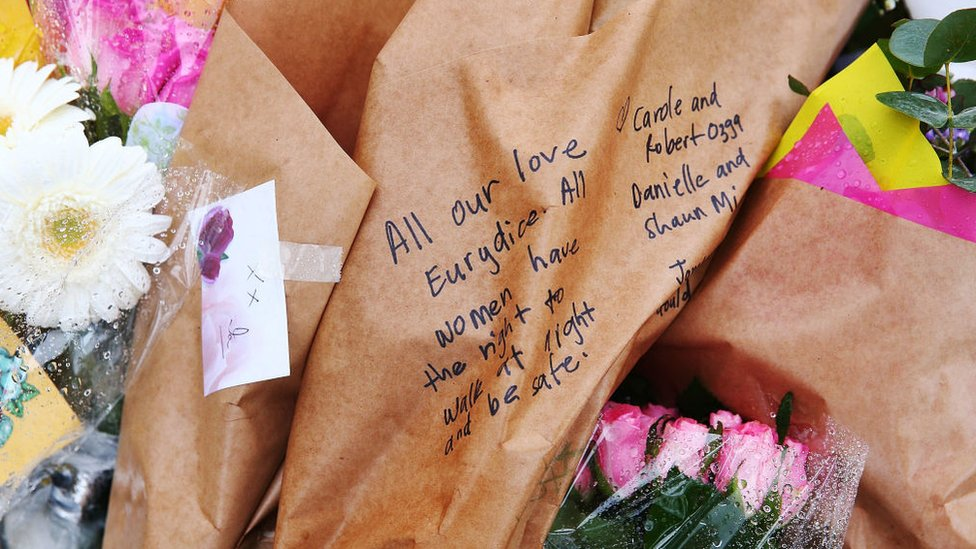 "A message on a bouquet tribute reads: ""All our love Eurydice. All women have the right to walk at night and be safe."""
