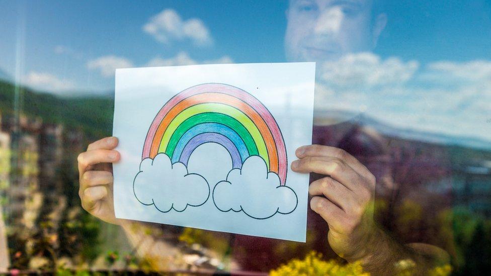 Hombre sosteniendo arcoíris en la ventana