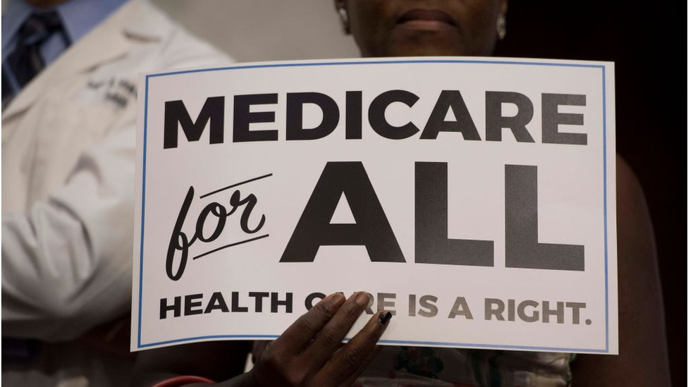 Woman holds sign reading Medicare for All - Healthcare is a right