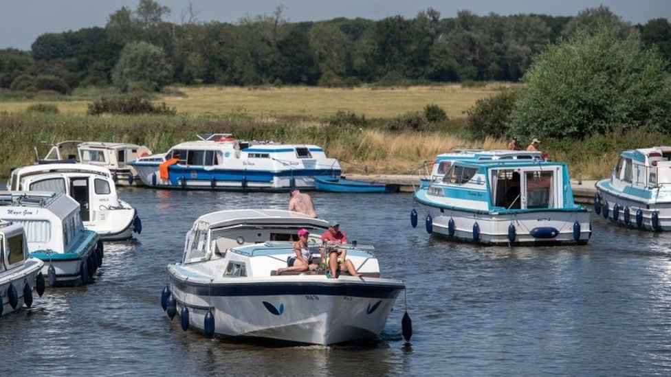 Pleasure boats make their way along the River Ant at Ludham Bridge on the Norfolk Broads