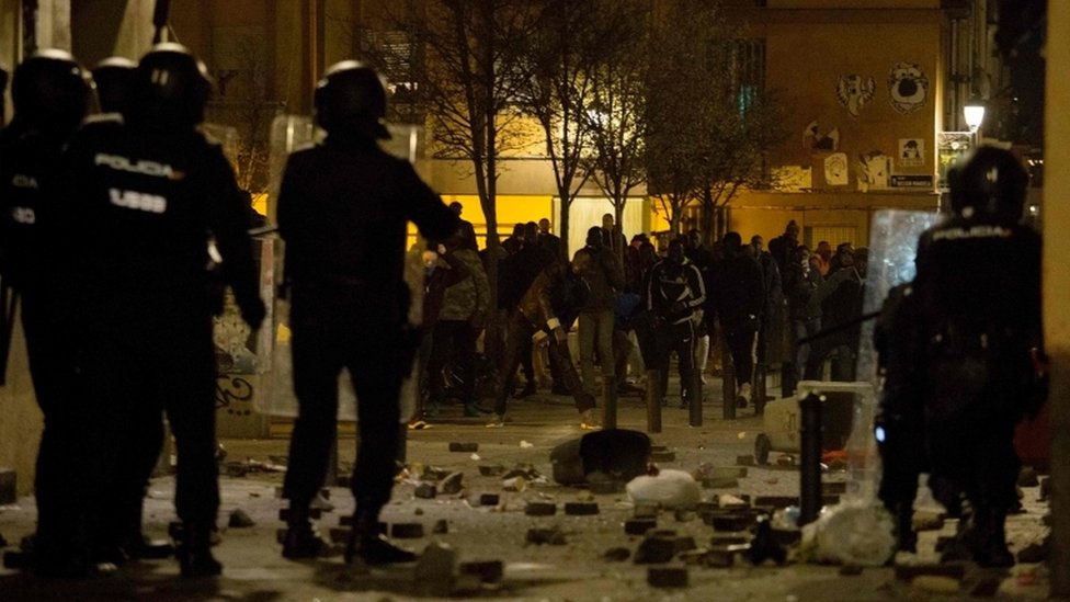A line of Spanish national police officers face a line of protesters in the street after dark in Madrid