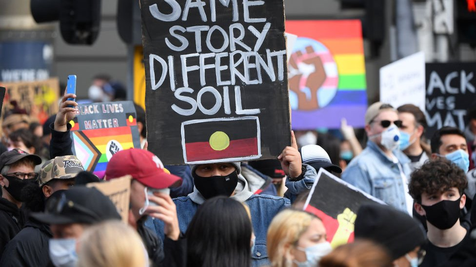 "A protests holds a placard with Aboriginal flag which says: ""Same story, different soil"""