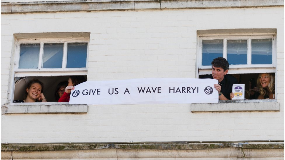 "Well-wishers hold a banner saying ""Give us a wave, Harry"""