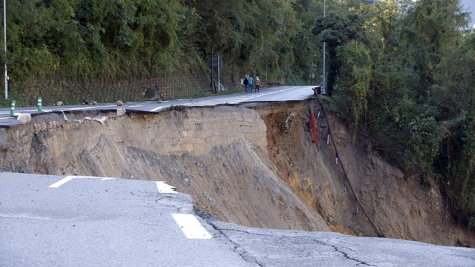People walk on a collapsed road along the Vésubie river that was partially washed away because of heavy rains brought by Storm Alex in Roquebillière, France, on 3 October 2020