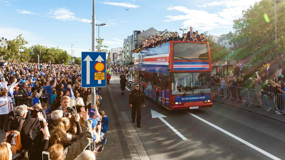 Iceland national football team arrives in Reykjavik on July 4, 2016 on a bus while people in the streets greet them as winners after they lost against France during the the Euro 2016 quarter-final football match between France and Iceland on the day before.