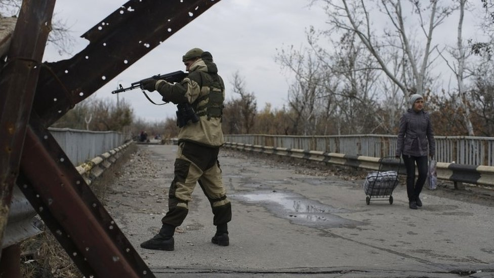 A Russia-backed rebel stands guard on a newly reconstructed bridge which connects rebel- and government-controlled territory in Stanytsia Luhanska, eastern Ukraine (27 October 2015)
