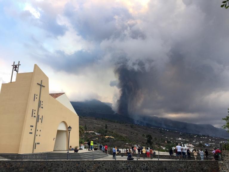 Una iglesia, personas y la columna del volcán La Palma de fondo.