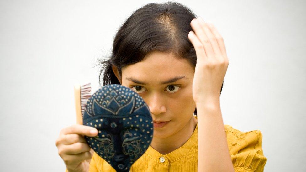 Mujer con principio de alopecia mirándose al espejo.