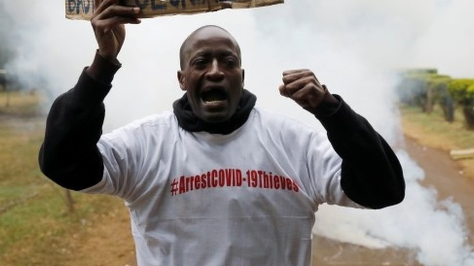A protester holds a placard as he is engulfed by tear gas during a demonstration against suspected corruption in the response of the Kenyan government to the coronavirus disease (COVID-19) outbreak, in Nairobi, Kenya, August 21, 2020