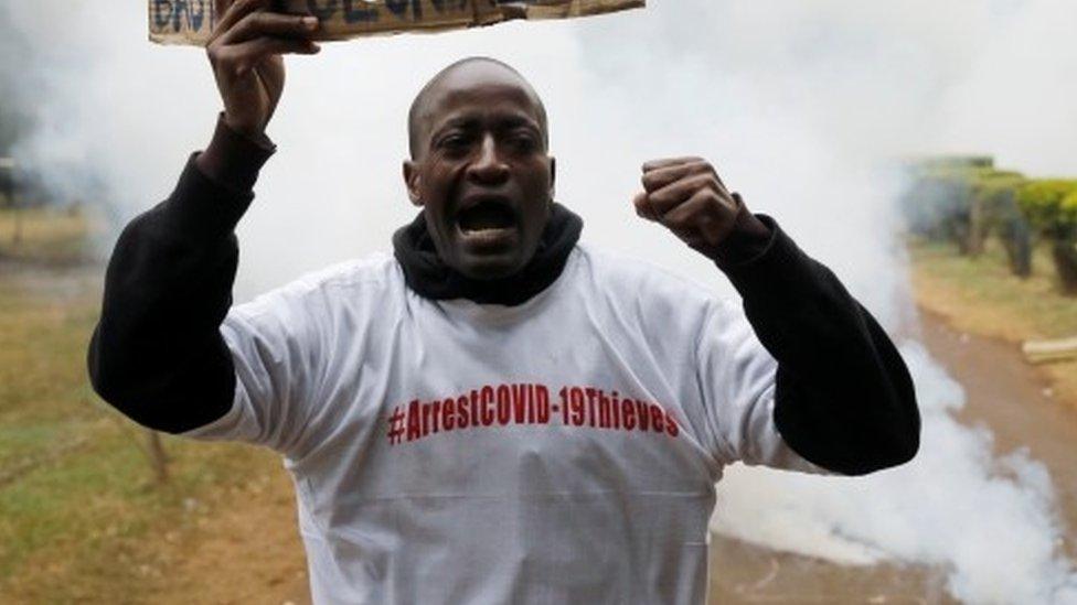 Um manifestante segura um cartaz ao ser engolfado por gás lacrimogêneo durante uma manifestação contra a suspeita de corrupção na resposta do governo queniano ao surto da doença coronavírus (COVID-19), em Nairóbi, Quênia, 21 de agosto de 2020