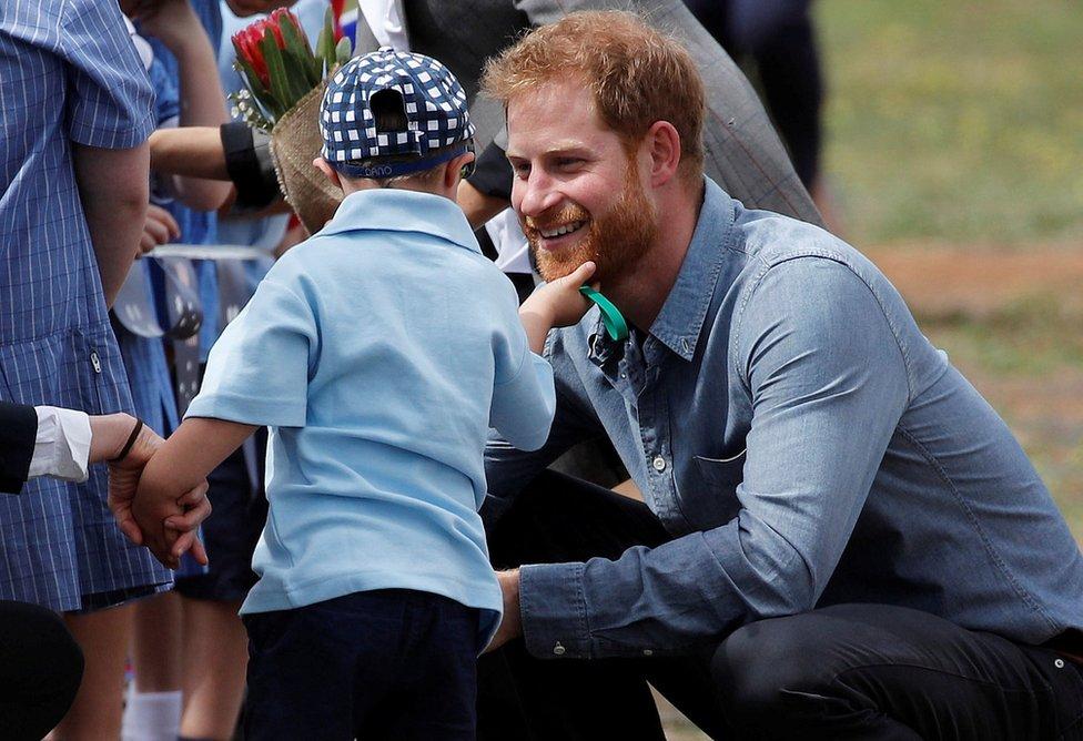 A young boy stroking Prince Harry's beard