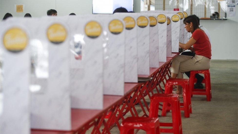 أشخاص يتناولون وجبات غذائية على طاولات منفصلة عن بعضها بحواجز بلاستيكية في محاولة لتطبيق إجراءات التباعد الاجتماعي في بانكوك، تايلند