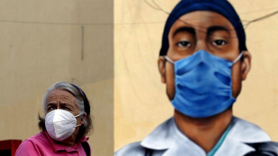 Una mujer con mascarilla frente a un mural en homenaje a los trabajadores de salud en Zapopán, México, el 12 de agosto de 2020.