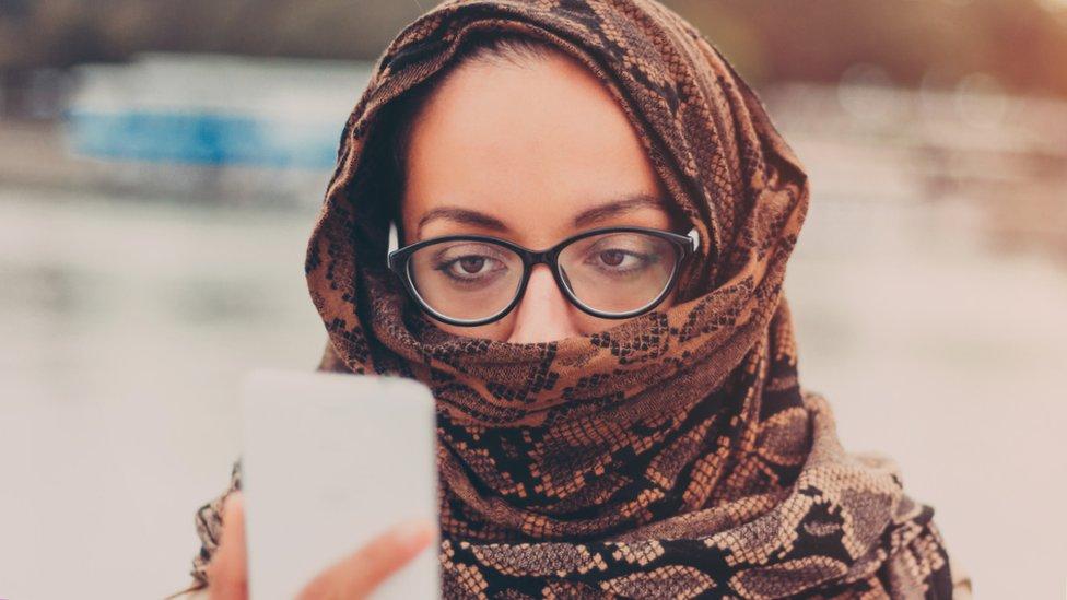امرأة تنظر إلى هاتف
