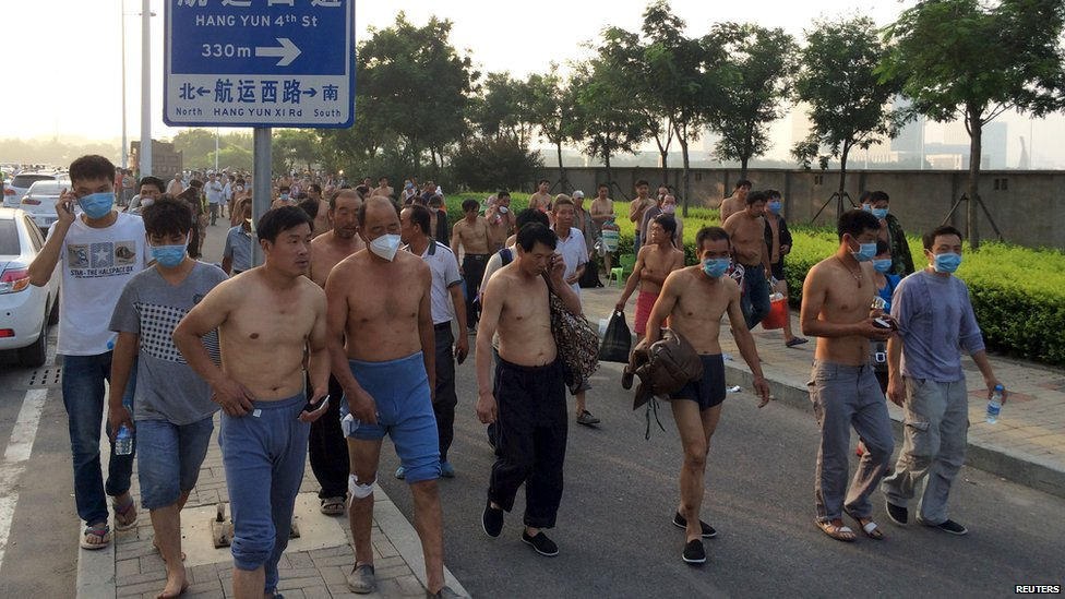 Tianjin residents walk through the streets after two massive explosions