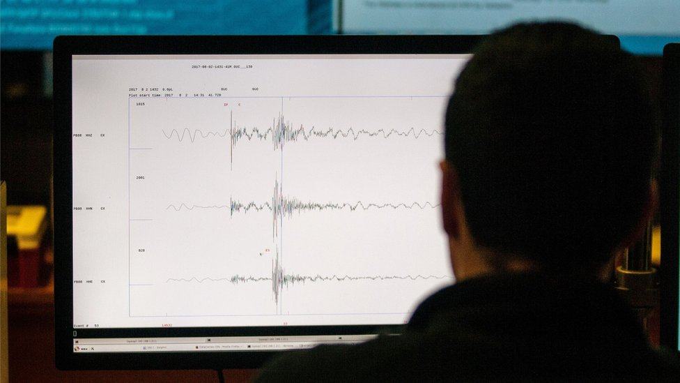 A screen with seismic waves on it, viewed over a man's shoulder