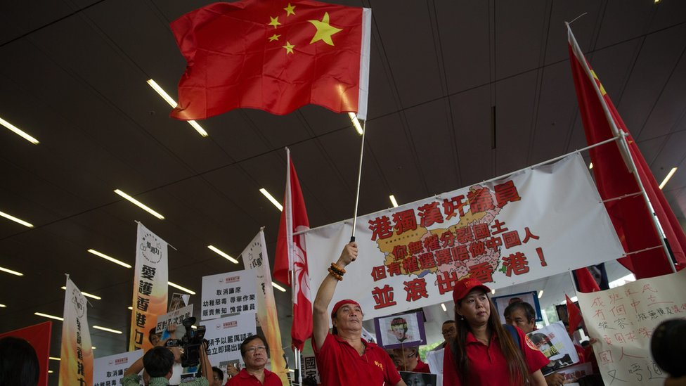 Pro-China supporters wave a People's Republic of China flag during a protest outside the Legislative Council in Hong Kong, China, 19 October 2016.