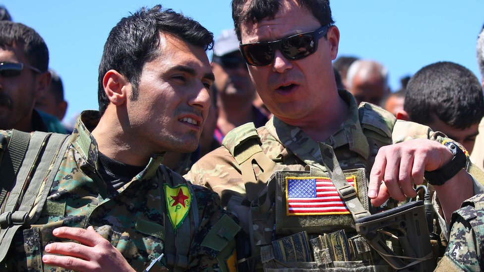 File photo from 25 April 2017 showing US military officer speaking to Syrian Kurdish People's Protection Units (YPG) fighter near Derik, Syria