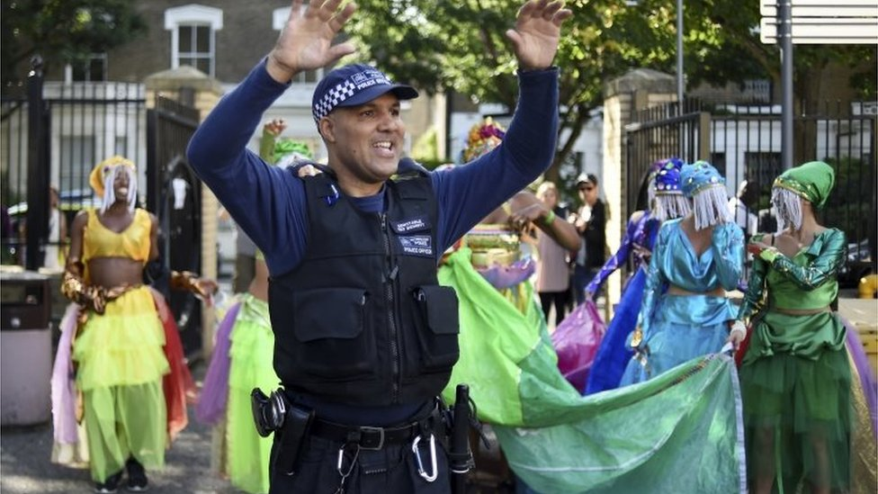 A police officer dances with a group of performers during the Notting Hill Carnival