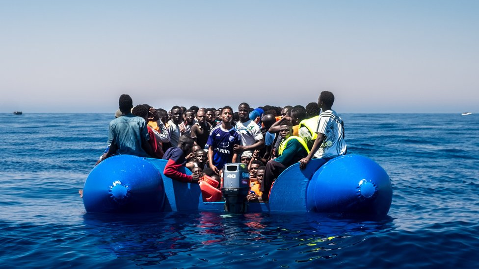 Refugees wait to get on onboard the rescue vessel Golfo Azzurro by members of the Spanish NGO Proactiva Open Arms, after being rescued from a wooden boat sailing out of control in the Mediterranean Sea near Libya on Thursday, June 15, 2017