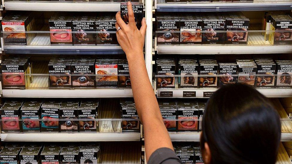 Un empleado en una tienda en Australia toma un paquete de cigarrillos de entre cajetillas idénticas.