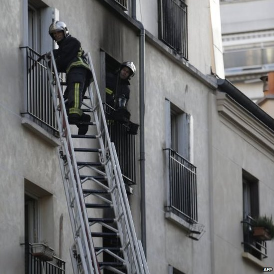 Firefighters use ladders to check the burnt apartment