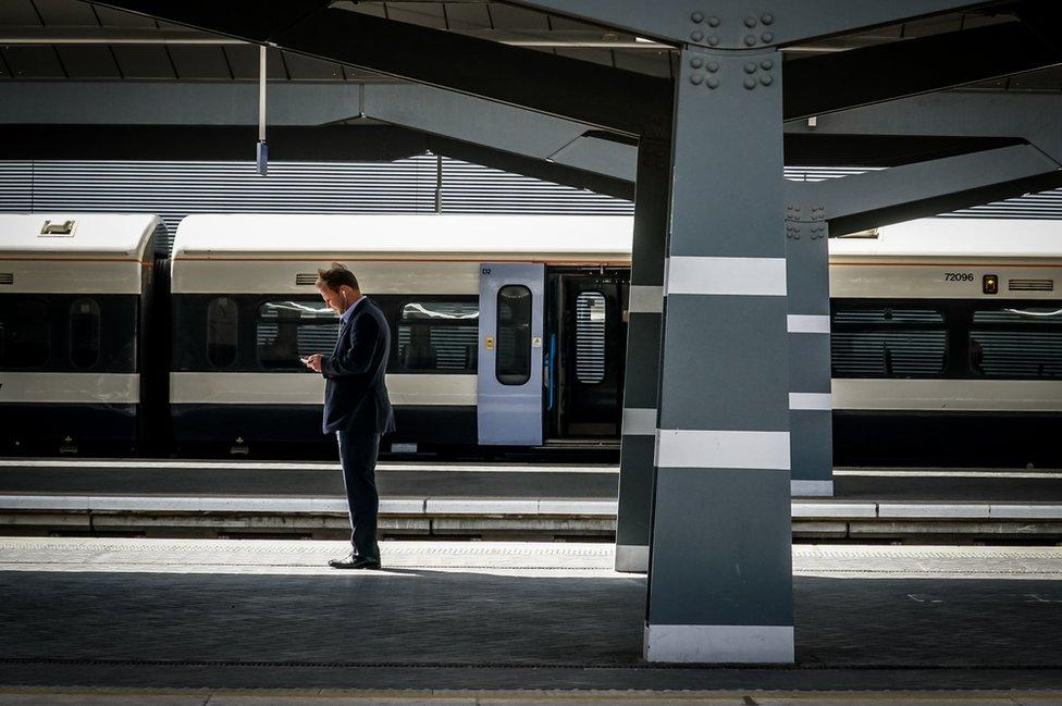 A man standing on a train station platform