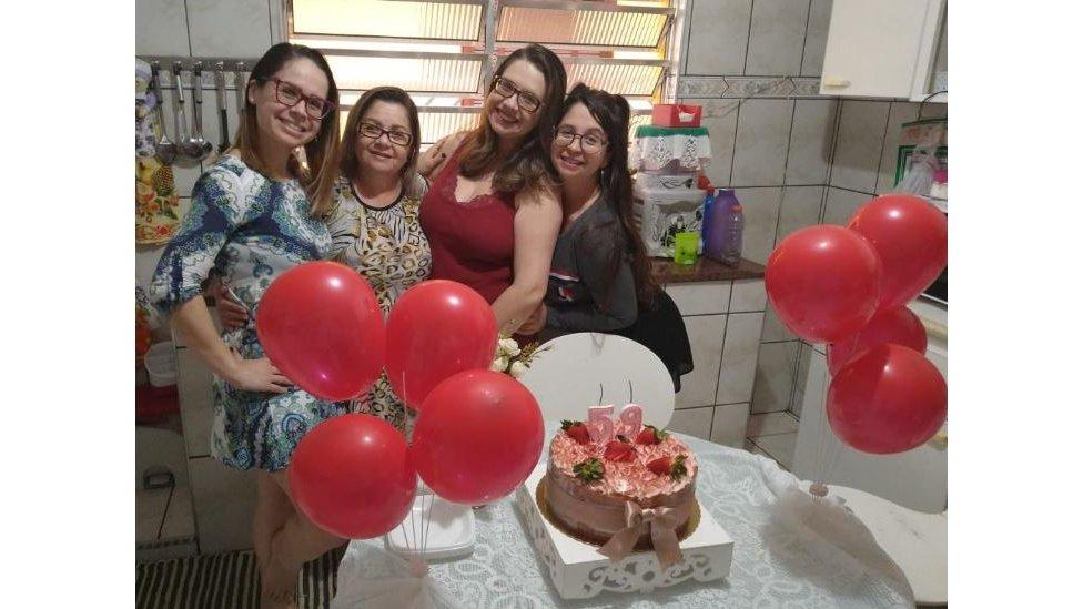 Ceci posa abraçada às três filhas em frente ao bolo de seu aniversário