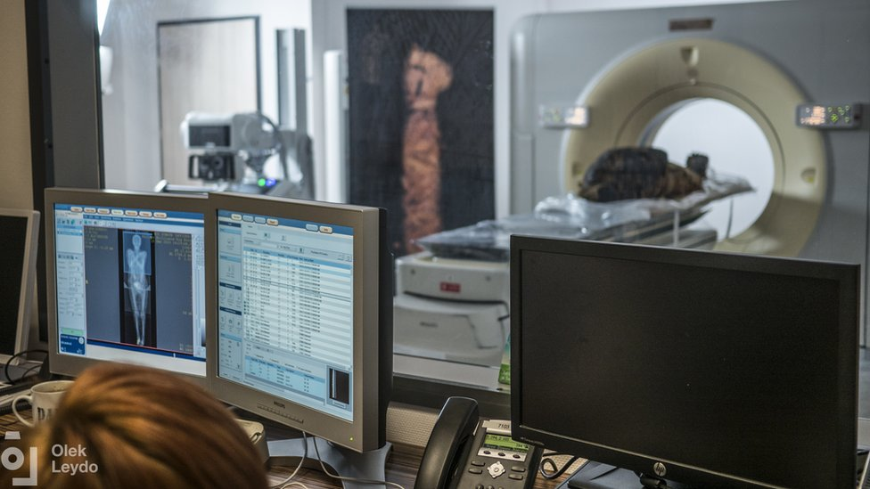 A mummy is seen going through CT scanner as scientists examine images