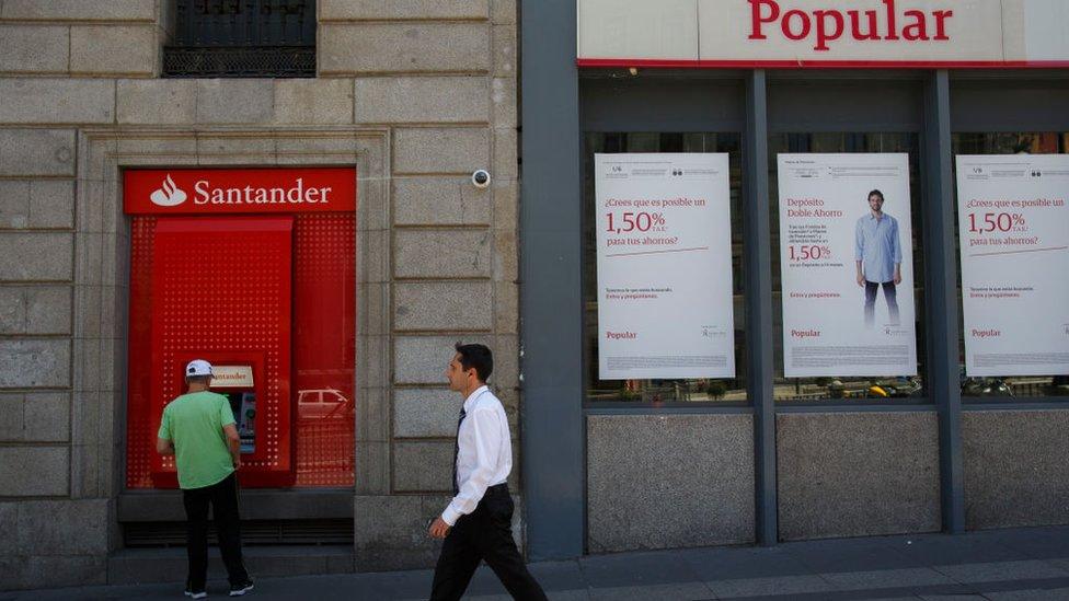 Hombre cruza frente a banco popular