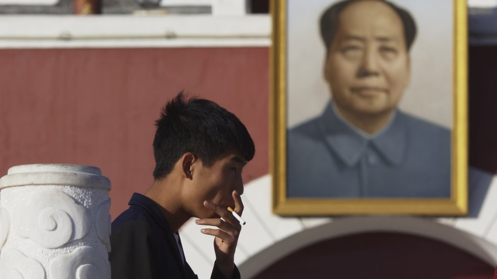A man smokes in front of a portrait of Chairman Mao