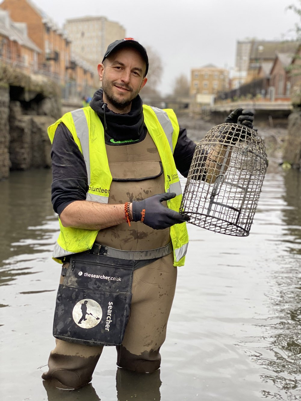 Simon Bourne, in full body waders, with a birdcage he found lying in the shallow water