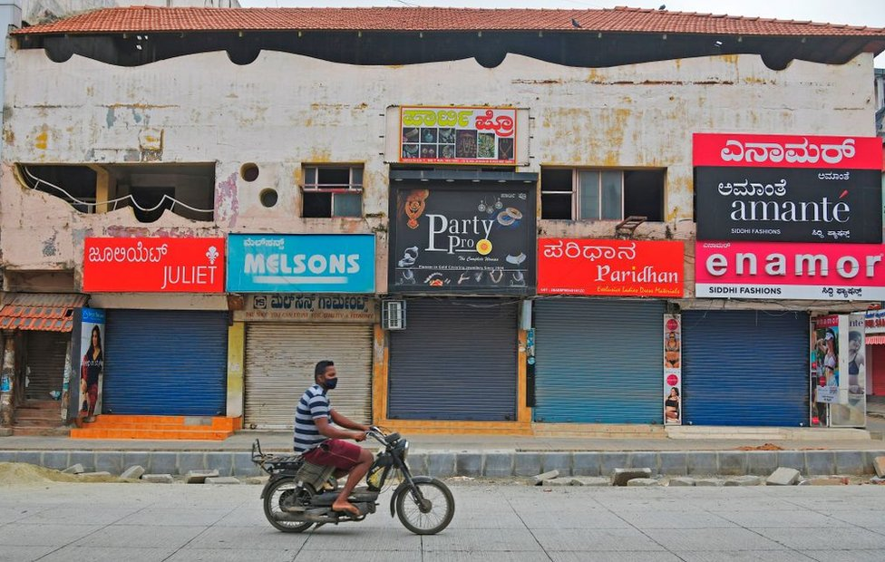 A man rides a two-wheeler in front of closed shops in a commercial area during a week-long lockdown to contain the surge of COVID-19 coronavirus cases, in Bangalore on July 15, 2020.
