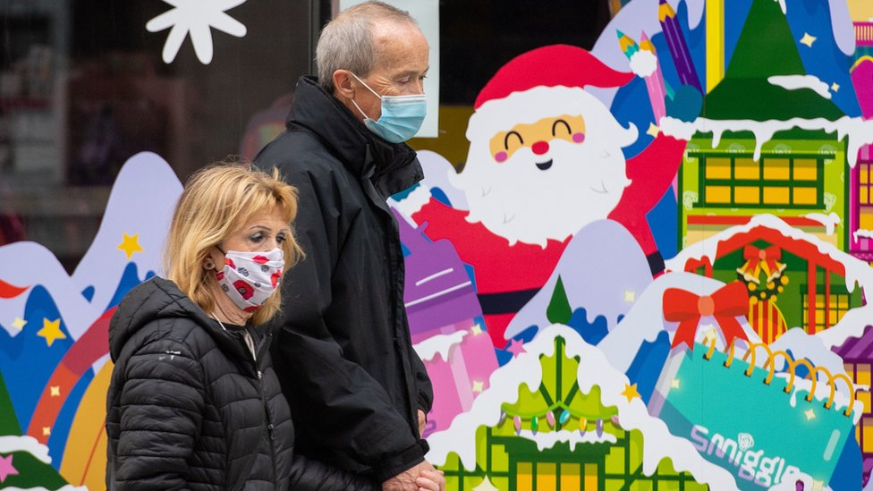 People wearing face masks pass a Christmas window display on Oxford Street