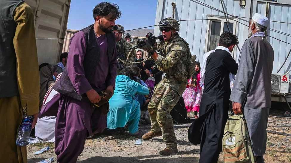 A US soldier points his gun towards an Afghan passenger at the Kabul airport in Kabul