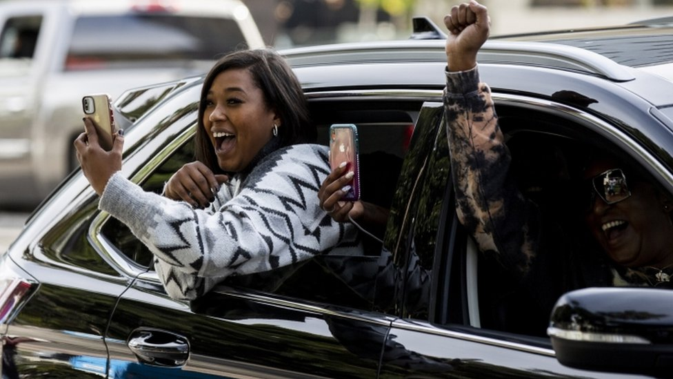 A woman uses her phone as she celebrates from a car
