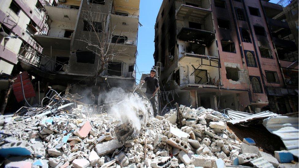 طفل يقف على أنقاض مبنى مدمر في مدينة دوما