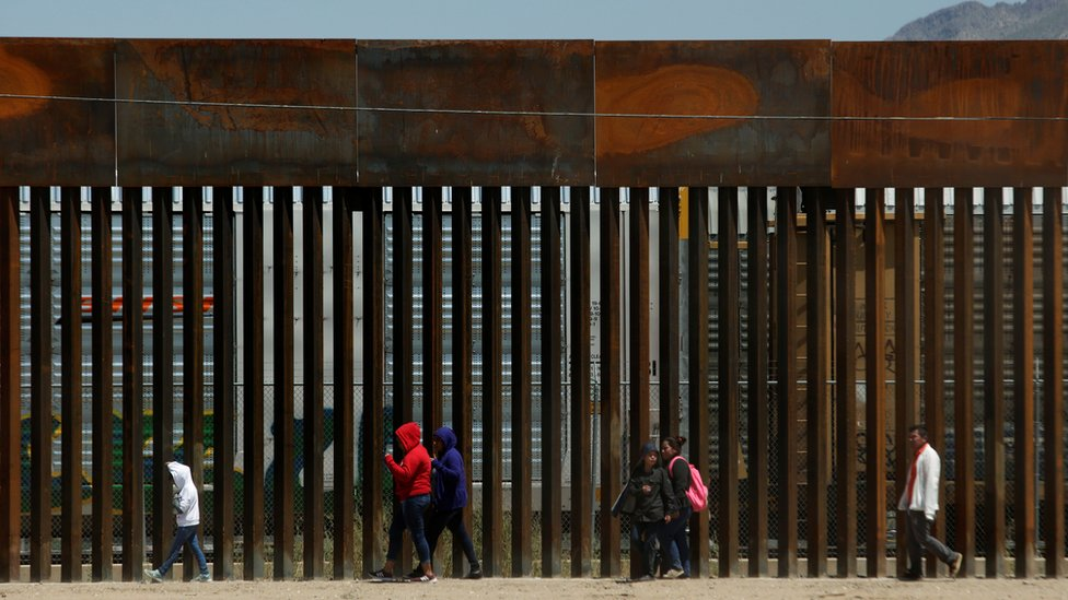 Migrants walk along the border fence after crossing illegally into El Paso, Texas