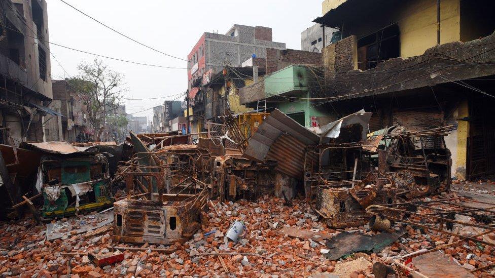 Polisi berjalan di atas puing-puing di daerah yang terkena dampak kerusuhan Shivpuri setelah bentrokan Citizenship Amendment Act (CAA) di Delhi