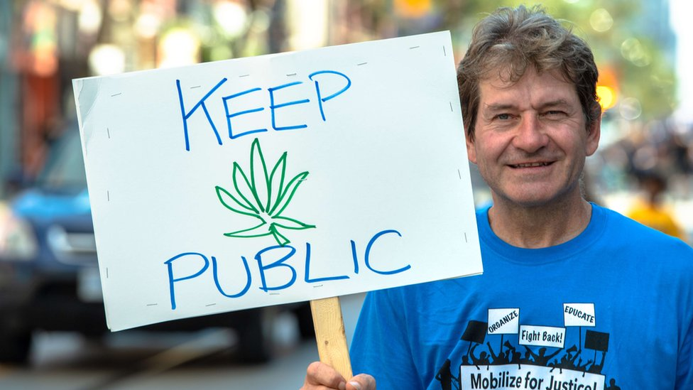 A man holds up a protests sign urging cannabis to be kept public
