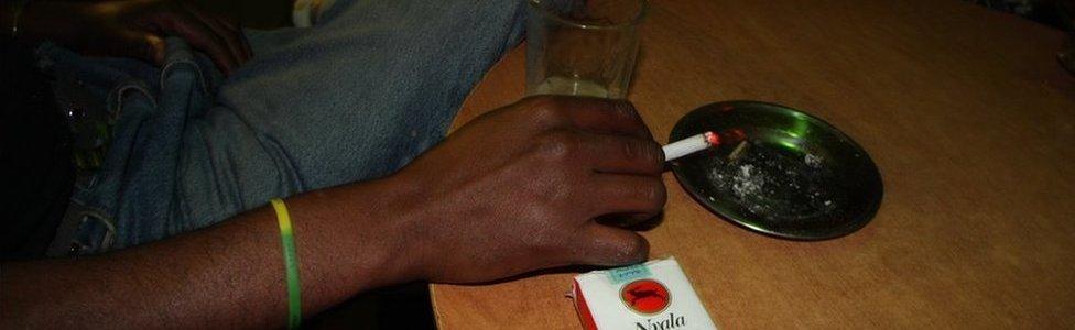 Inside a bar off Bole Road a man smokes Nyala, Ethiopia's locally made cigarette brand.