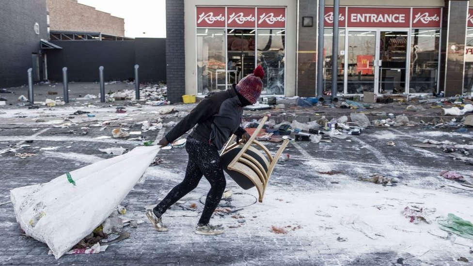 A suspected looter pulls a few items along the ground outside a vandalised mall in Vosloorus, on the outskirts of Johannesburg,